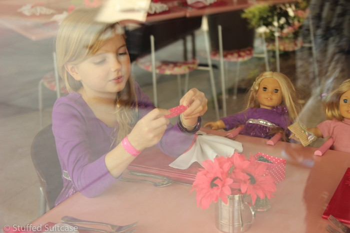 A peek inside at Faith reading some conversation starters at the American Girl Seattle Bistro
