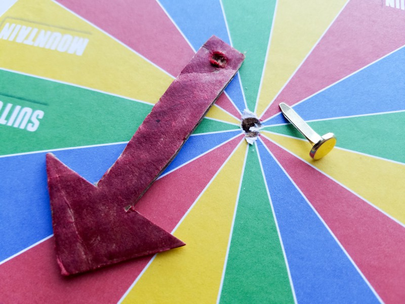 Make an arrow (we used cardboard) and fasten to center of spinner