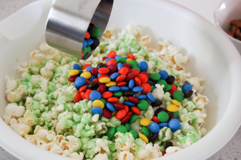 Mix together your popcorn, green sugar coating, pretzels and M&Ms