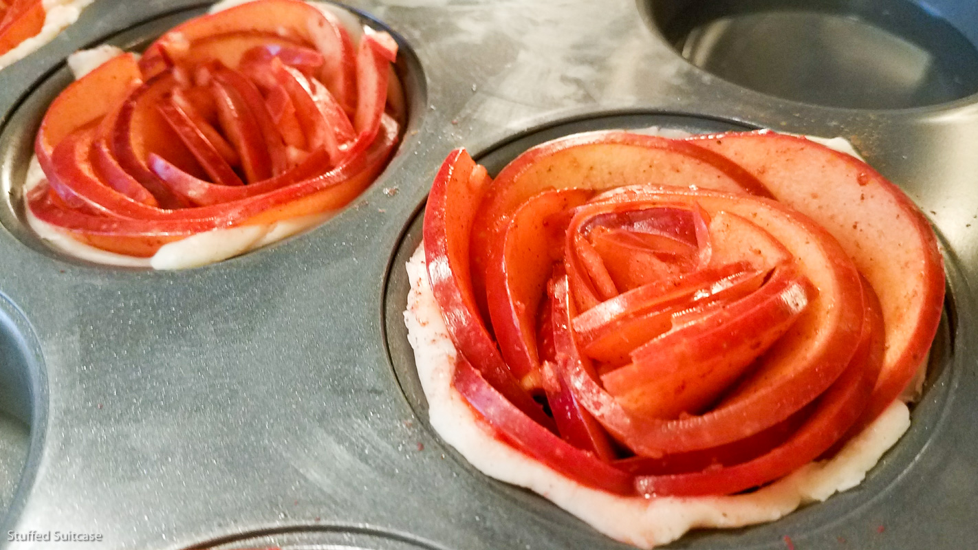 Roll cinnamon seasoned apple slices and place in cupcake pans to make rose apple pies © Stuffed Suitcase