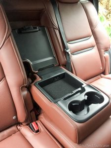 Backseat center seat drop-down console features cup holders and USB charge ports | © Stuffed Suitcase