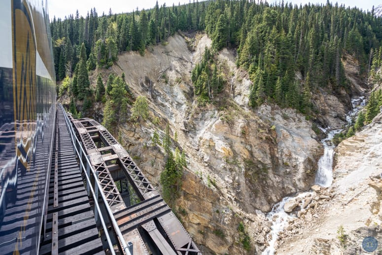 Rocky Mountaineer train crossing bridge in Canadian Rockies