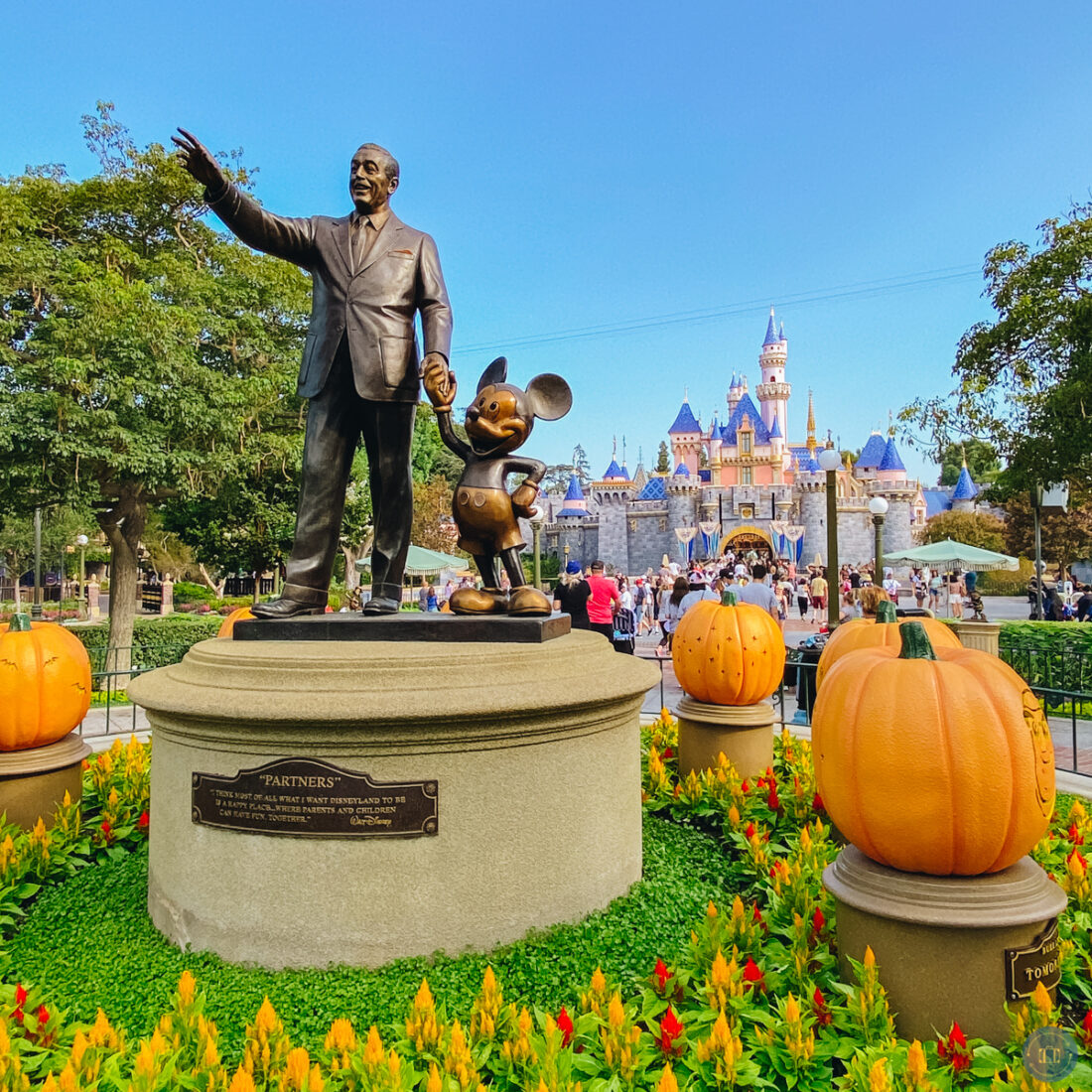 partners statue at disneyland with pumpkins and castle