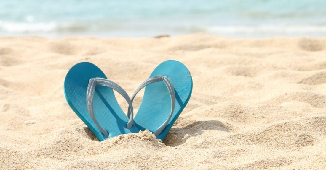 flip flops in the sand. photo credit canva