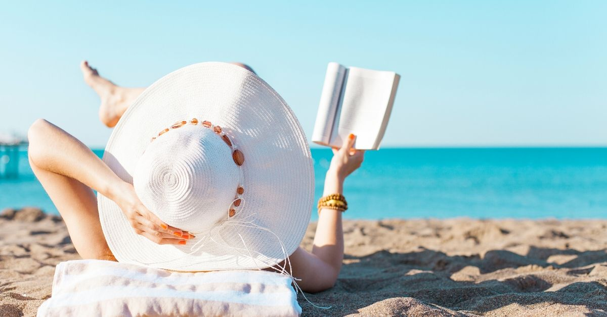 woman on beach reading a book. photo credit canva