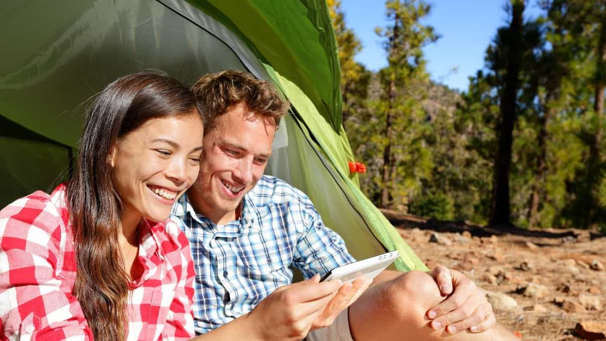 couple on phone camping in tent