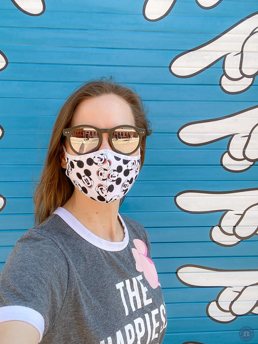 kim tate in mask standing in front of mickey hand d23 photo mural at disney california adventure park