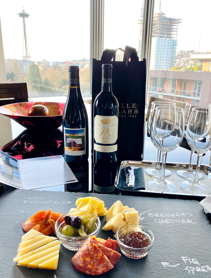 wine bottles and cheese platter on table with space needle in the distance