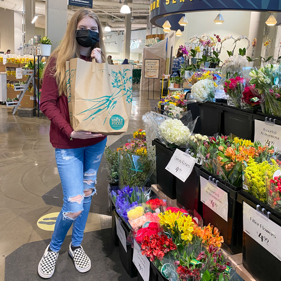 girl holding whole foods grocery bag near flowers in store