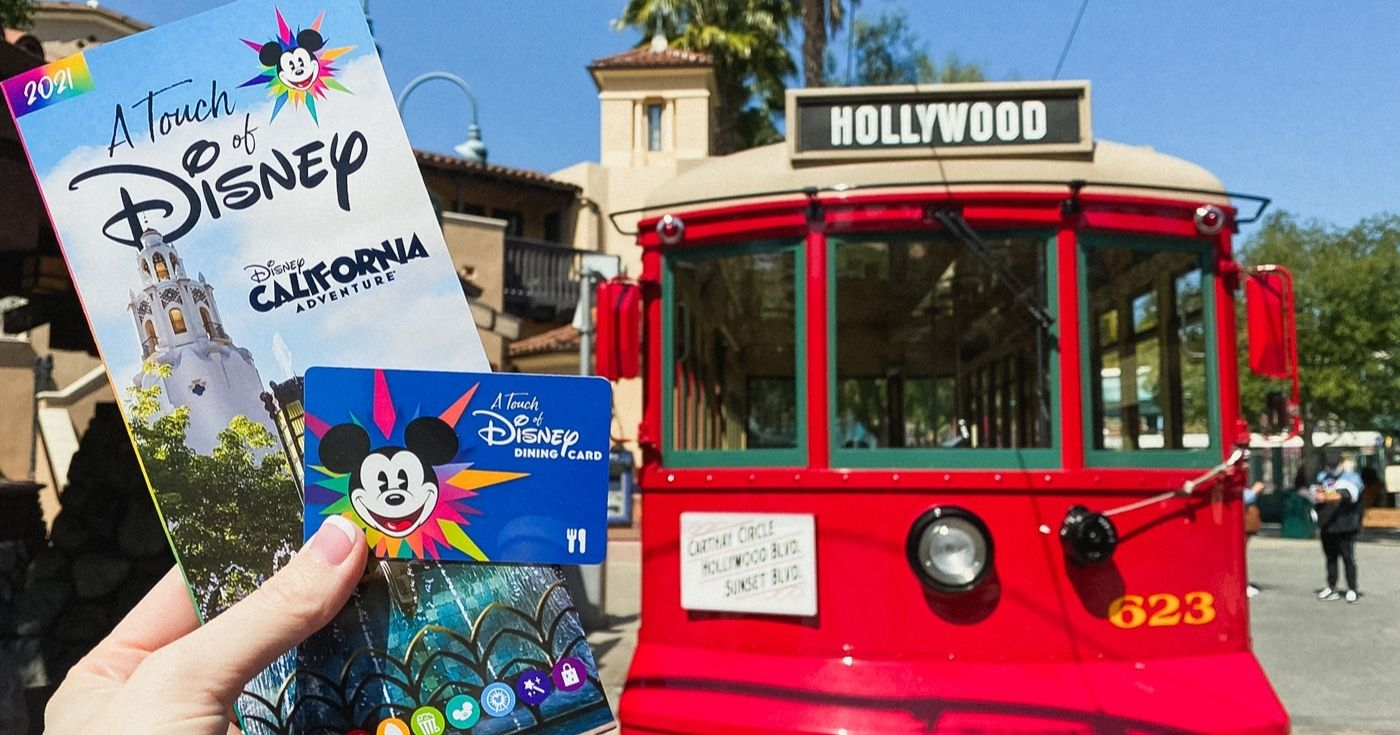 holding touch of disney park map and dining card in front of red trolley at Disney California Adventure Disneyland