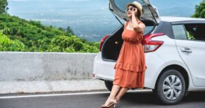 girl in dress next to car on road trip overlooking city