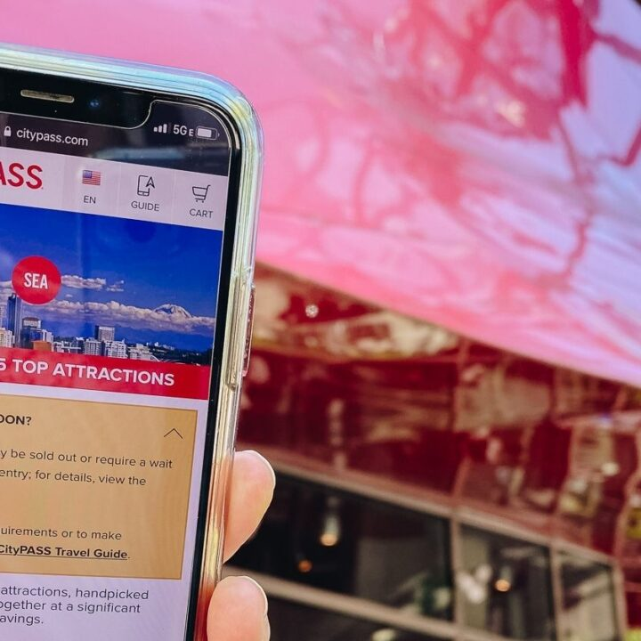 hand holding phone with citypass seattle screen outside of mopop museum