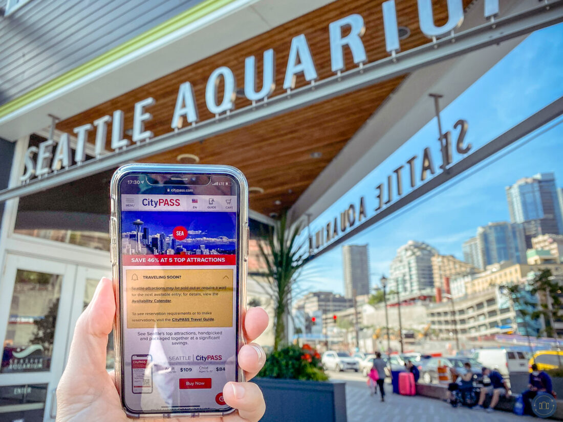 holding phone with citypass seattle screen in front of seattle aquarium entrance