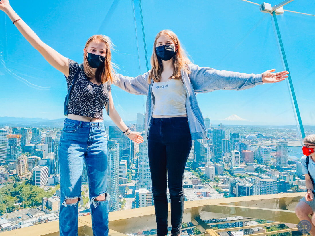 girls standing against glass at top of seattle space needle
