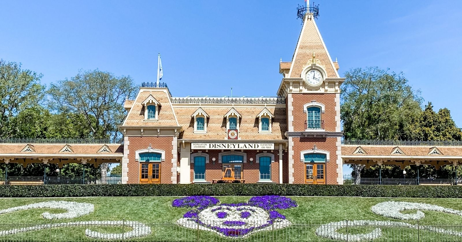 disneyland railroad at park entrance with mickey head floral design in front