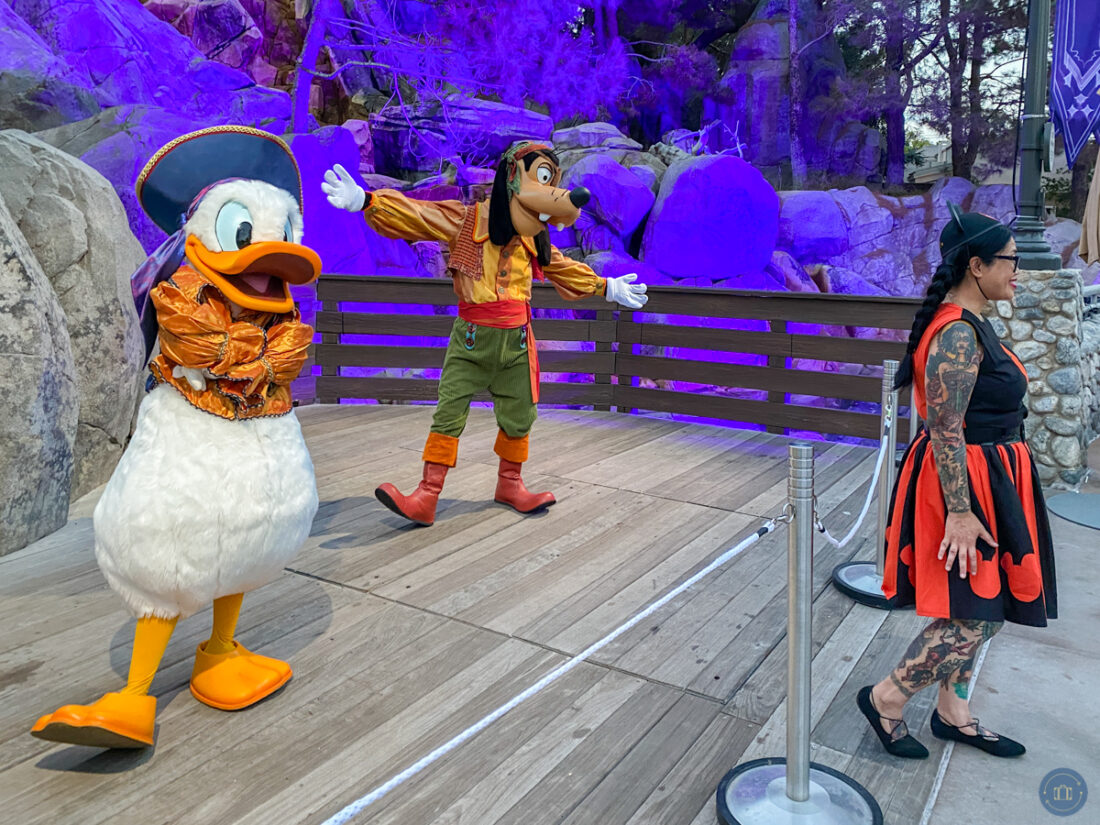 girl getting photo with disney characters donald duck and goofy at oogie boogie bash party