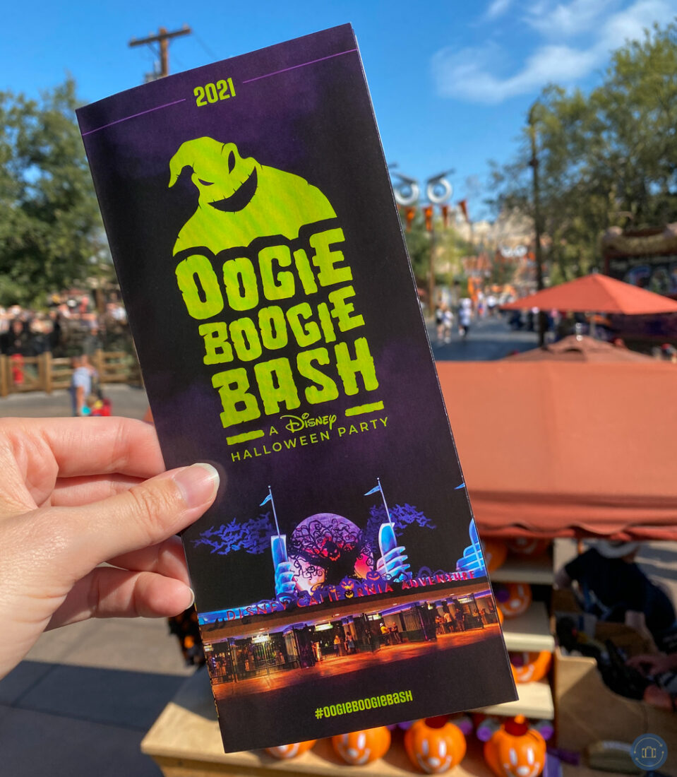 hand holding pamphlet for 2021 oogie boogie bash halloween party at disneyland