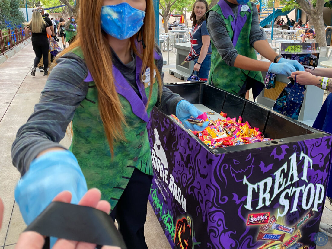 getting candy at a treat trail station at disneyland oogie boogie bash